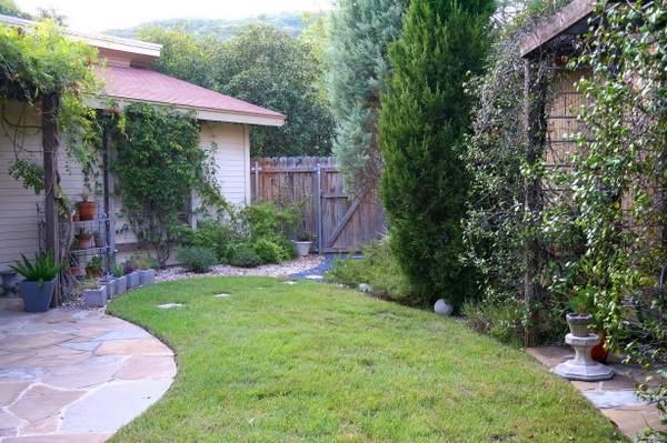 Внешний вид двора с деревьями, вьющимися растениями и гравием